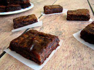 caramel brownies on white paper on a table