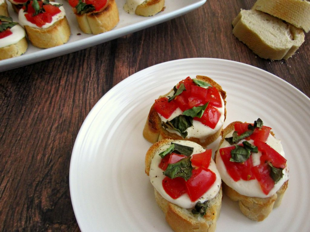 French bread slices, topped with fresh basil, mozzarella cheese, and vine-ripened tomatoes created these delicious Caprese Bites.