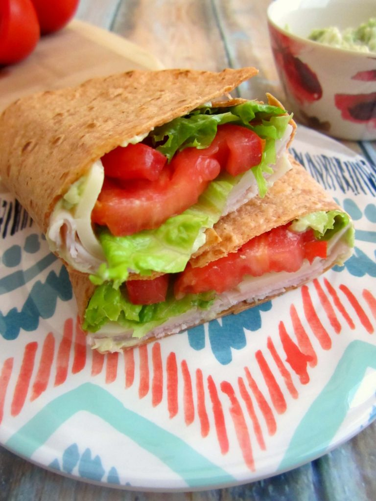 Fresh turkey slices, provolone cheese, tomatoes, and lettuce envelope a whole wheat wrap, topped with avocado mayonnaise.