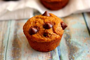a single chocolate chip pumpkin muffin on wood