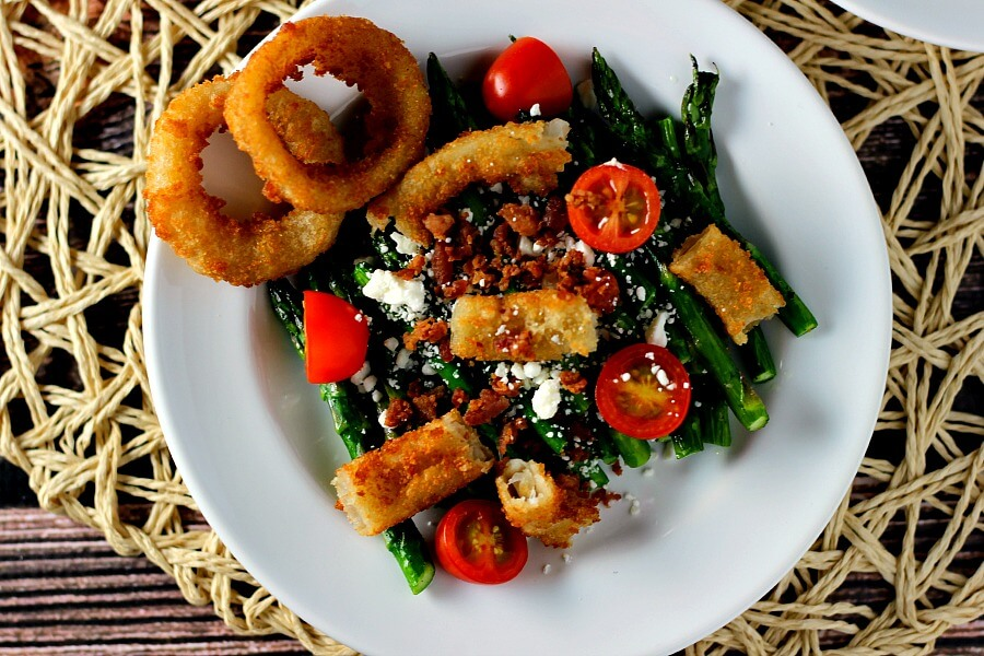 This Asparagus Onion Ring Salad combines fresh asparagus, Alexia onion rings, cherry tomatoes, feta cheese, bacon bits, and a drizzle of balsamic dressing.