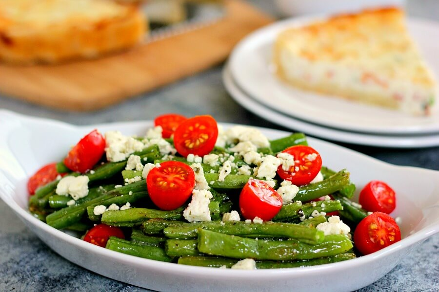 This Roasted Garlic Green Bean Salad is filled with fresh beans, ripe tomatoes and feta cheese, combined with a light garlic and lemon dressing!