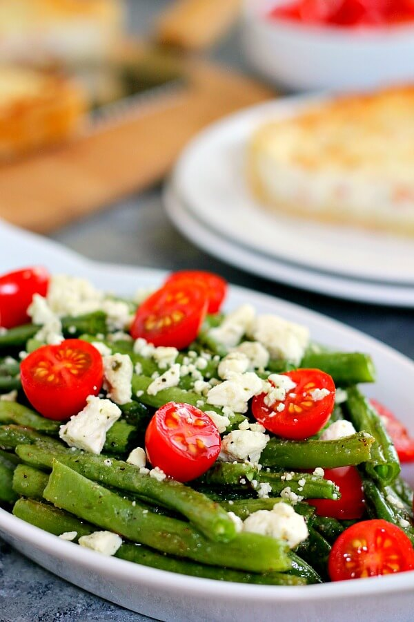 Roasted Garlic Green Beans are filled with fresh beans, ripe tomatoes and feta cheese, combined with a light garlic and lemon dressing! #greenbeans #greenbeanrecipe #roastedgreenbeans #vegetables #roastedvegetables #sidedish #easysidedish