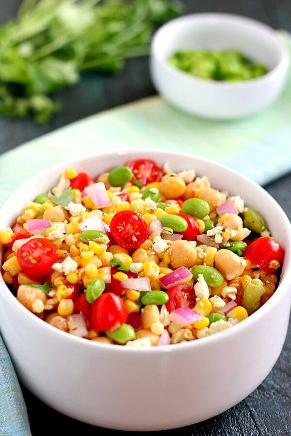 Jam-packed with corn, edamame, chickpeas, and tomatoes, this Corn, Edamame, and Chickpea Salad is full of flavor and makes the perfect light lunch or dinner. By adding a touch of feta cheese, red onion, cilantro, lime juice, and a white balsamic dressing, the ingredients blend together to make a zesty dish!