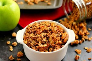 apple pie granola in a dish in front of a baking pan