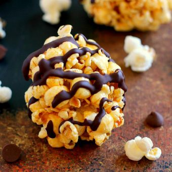 These Caramel Popcorn Balls combine fresh popcorn, caramel sauce, marshmallows, and dark chocolate. This easy snack is perfect to munch on when you need to satisfy those sweet and salty cravings!