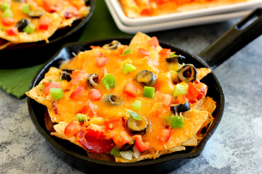 These Pizza Skillet Nachos are packed with two kinds of cheese, hearty pepperoni, black olives, tomatoes, and green peppers. Filled with classic pizza toppings, this is the perfect snack to munch on while relaxing on game day!
