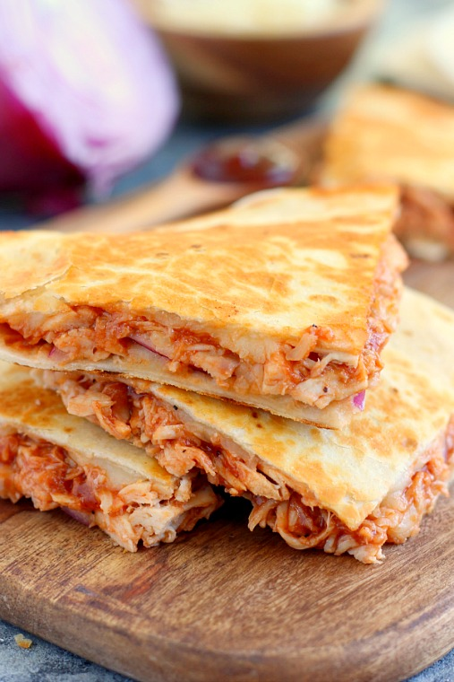 a stack of three sections of a bbq chicken quesadilla