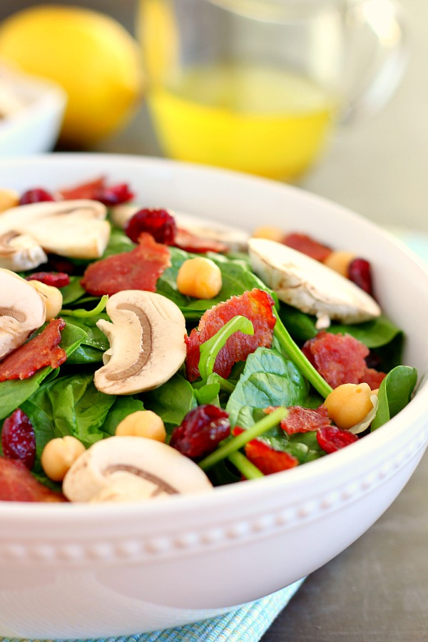This Cranberry Mushroom Spinach Salad with Lemon Basil Vinaigrette combines baby spinach leaves, dried cranberries, fresh mushrooms, chickpeas, and crumbled bacon, all tossed with a lemon basil dressing. This dish is easy to throw together and serves as the perfect lunch or dinner! #spinachsalad #cranberries #mushroom #mushroomsalad #cranberrysalad #saladrecipes #healthysalad #thanksgiving #lunch