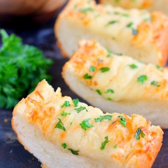 This Cheesy Garlic Bread is packed with buttery spread that's combined with garlic and then topped with Parmesan and mozzarella cheeses. It bakes up crispy and full of flavor. If you're looking for the perfect garlic bread to make, then this is it!