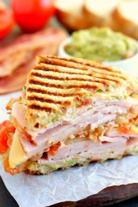 side shot of panini sandwich with turkey, bacon, and guacamole