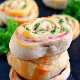 These Baked Ham and Cheese Roll-Ups contain just three ingredients and are ready in less than 20 minutes. Filled with deli ham, swiss cheese, and rolled up in a pre-made pizza dough, these roll-ups are sure to be the hit of the dinner table!