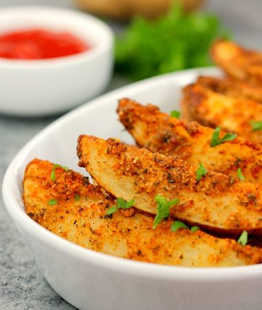 baked garlic parmesan potato wedges in a white bowl