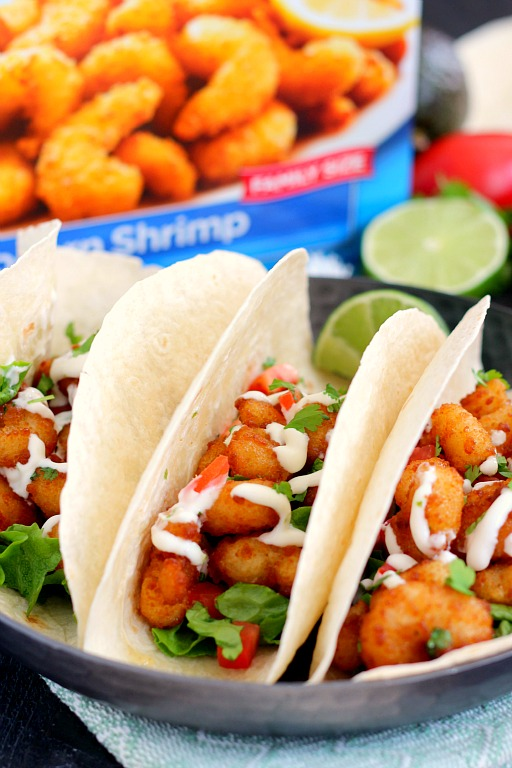 These Cilantro Lime Popcorn Shrimp Tacos are filled with crispy popcorn shrimp, a zesty cilantro lime sauce, and topped with a lime cream drizzle. Easy to make and ready in just 20 minutes, this flavorful dish will be the hit of your dinner table! #shrimp #popcornshrimp #tacos #shrimptacos #popcornshrimptacos #tacotuesday #seafood #seafoodtacos #easydinner