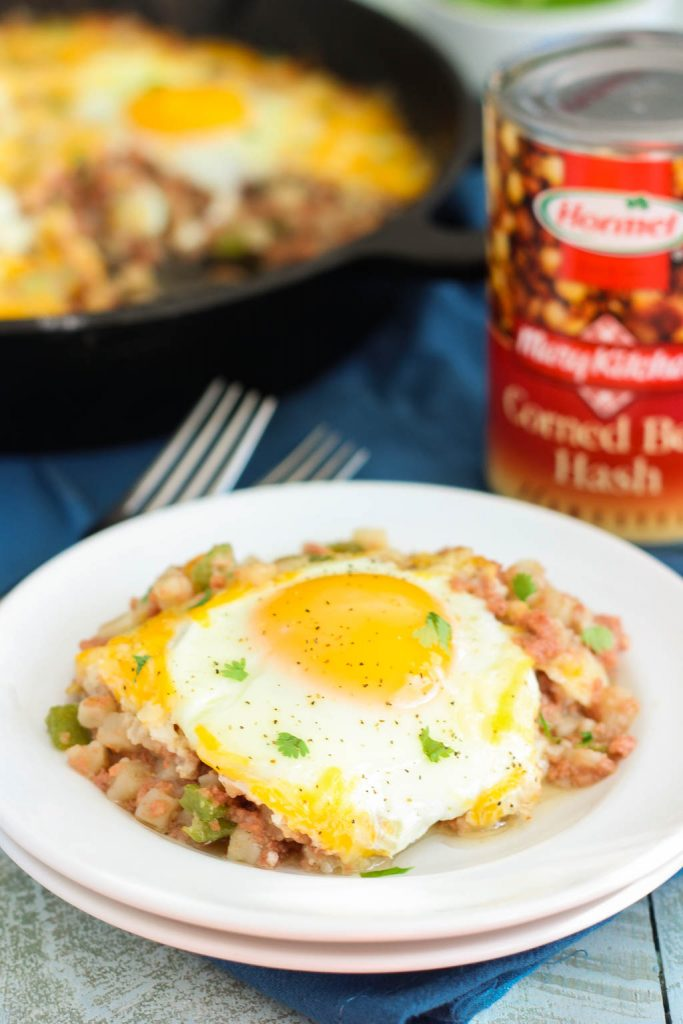 a serving of corned beef and eggs on a small plate. A can of corned beef and a skillet of corned beef hash rest in the background.