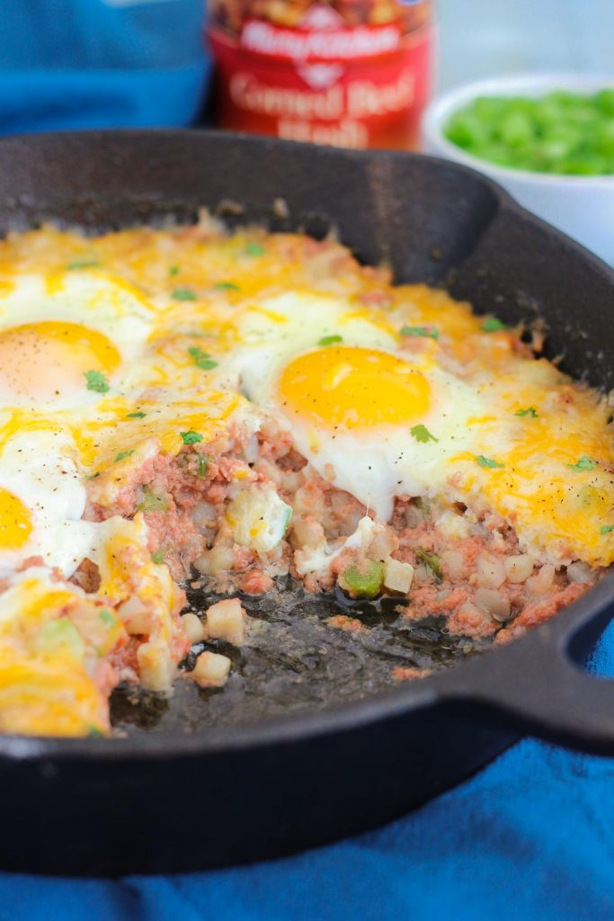 canned corned beef hash and eggs in a cast iron skillet. A portion has been scooped out.