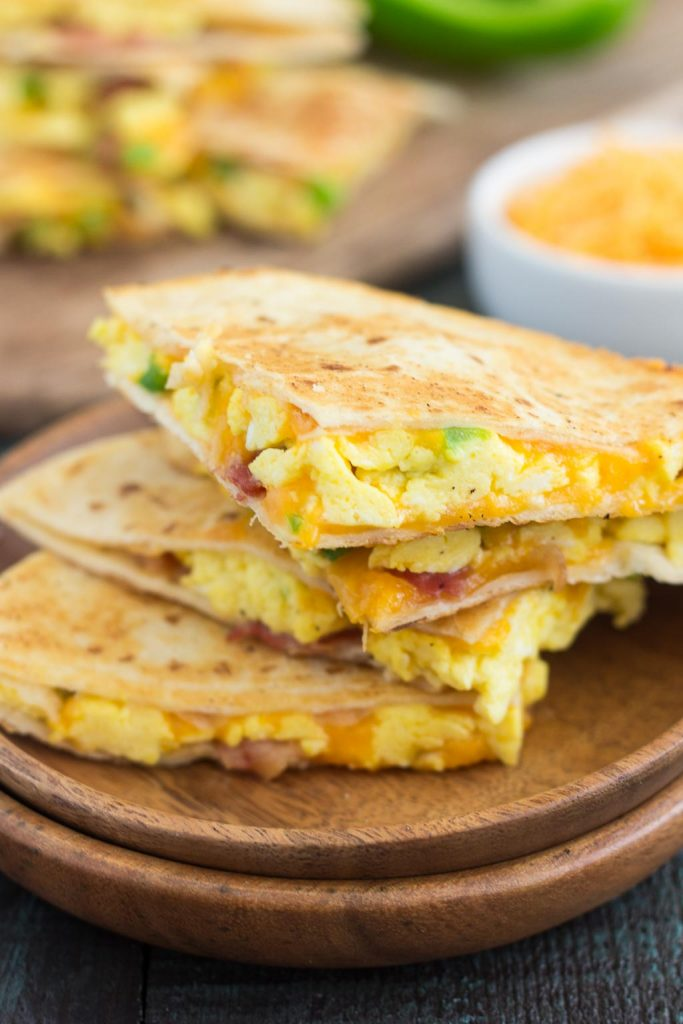 These Easy Breakfast Quesadillas are filled with fluffy, scrambled eggs, green peppers, bacon and cheddar cheeses, all enveloped between two crispy tortilla shells. It's an easy meal that's perfect for busy mornings! #quesadilla #breakfastquesadilla #eggs #breakfast #quesadillarecipe #easybreakfast #recipe