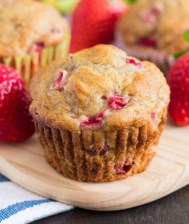 a strawberry banana muffin on a cutting board surrounded by strawberries