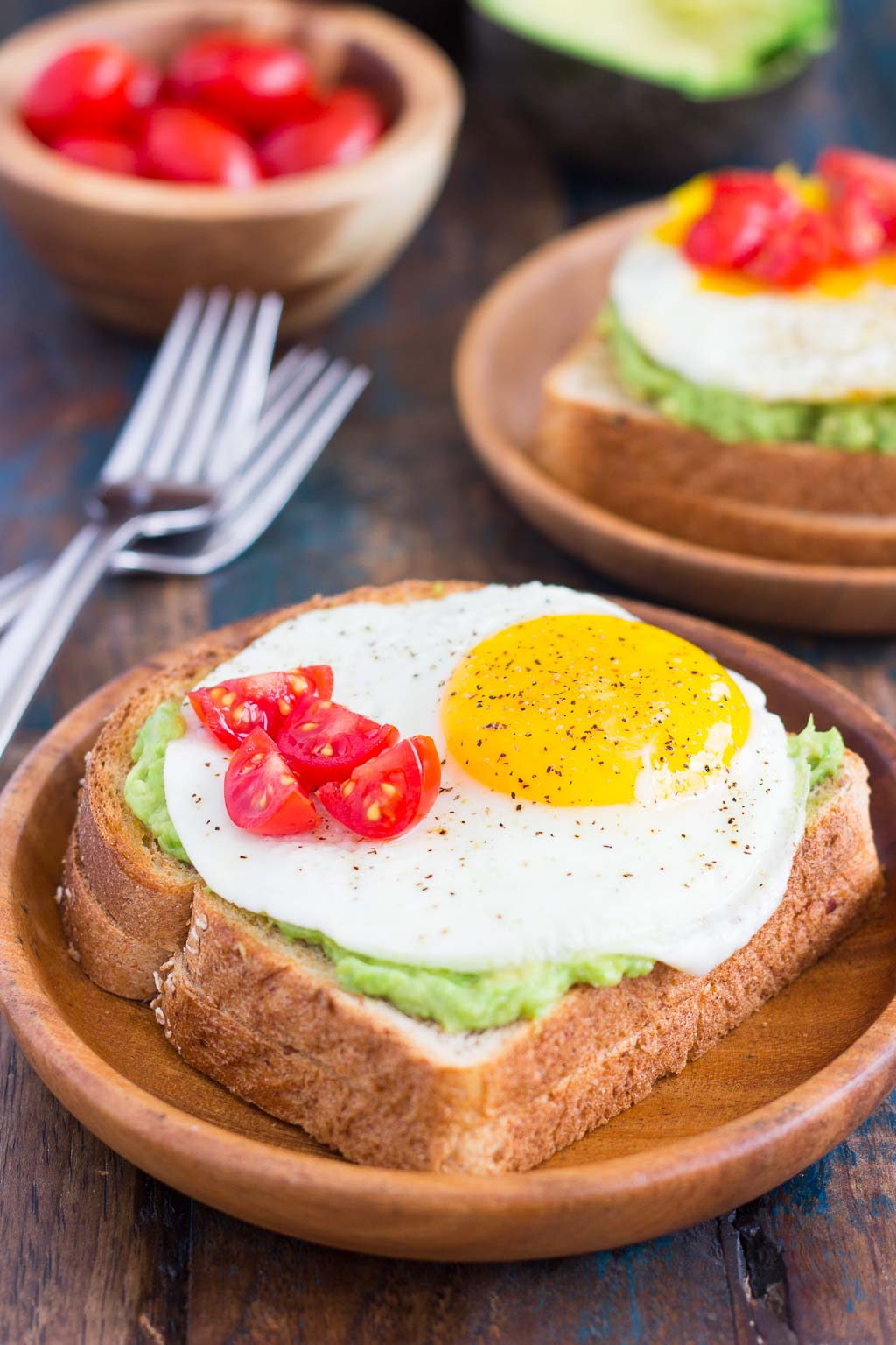 This Fried Egg and Avocado Toast is a deliciously simple way to jazz up your breakfast or snack. Hearty bread is toasted and then topped with mashed avocado, a fried egg, and cherry tomatoes. It's ready in just minutes and is full of healthy ingredients!