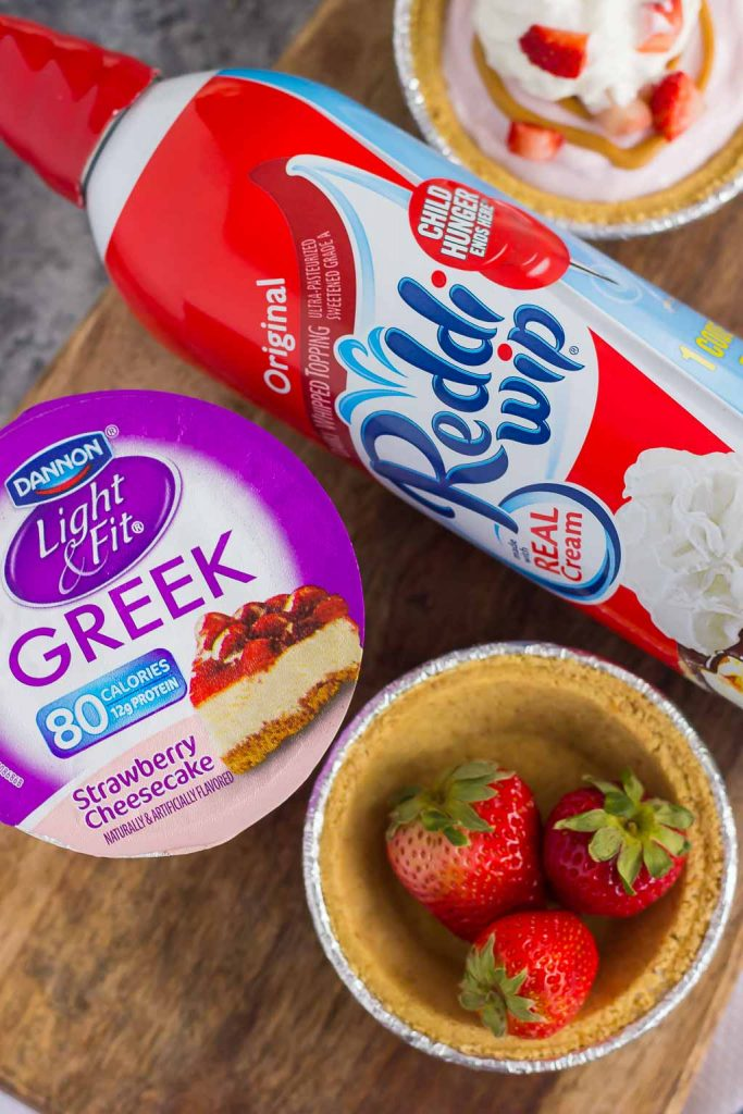 These Mini Strawberry Peanut Butter Cheesecake Pies are filled with Dannon® Light & Fit® Strawberry Cheesecake Greek Yogurt, creamy peanut butter, and fresh strawberries. Easy to make and packed with flavor, you can enjoy this no-bake, simple dessert that's perfect for the warmer weather!