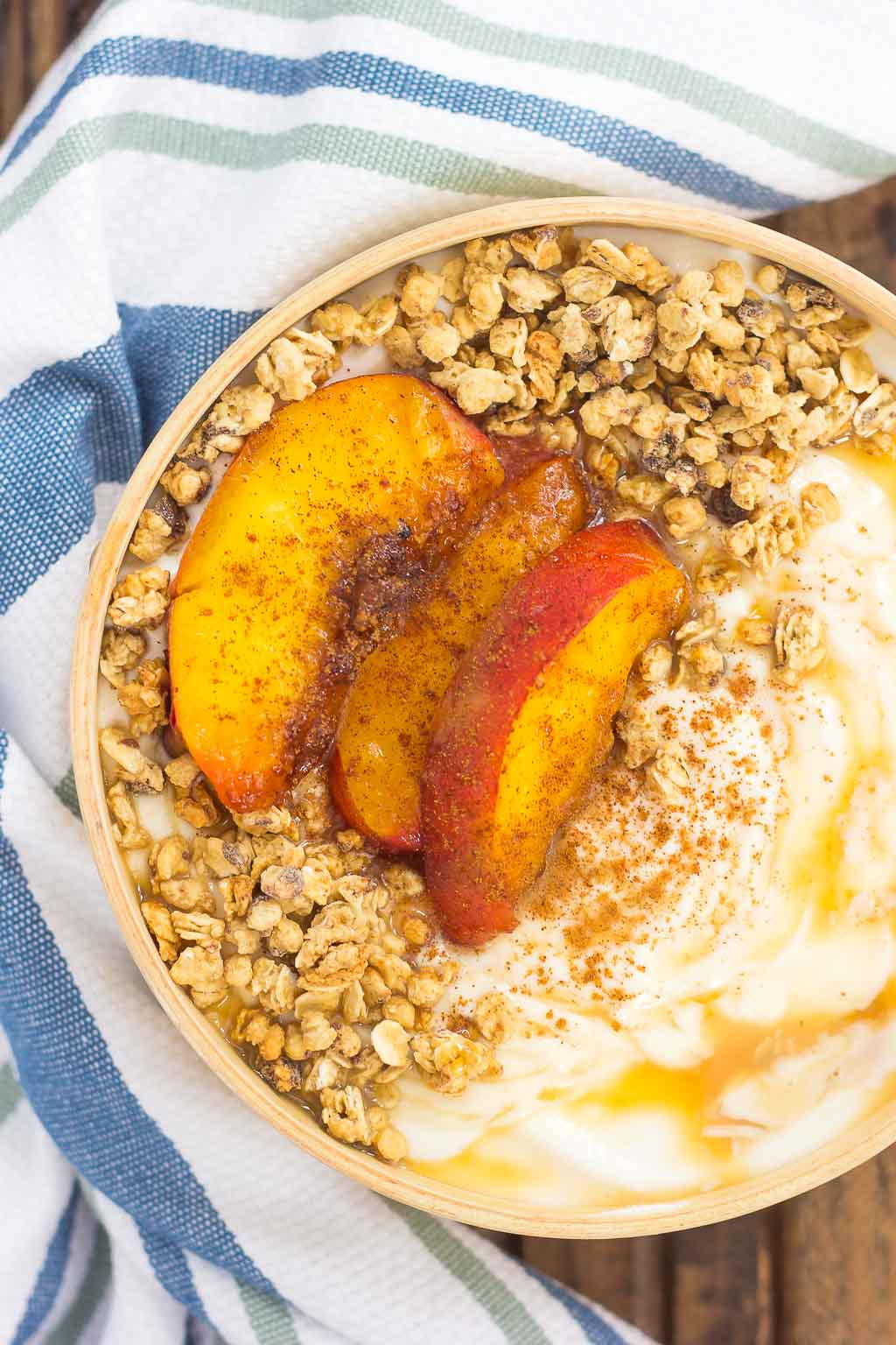 This Grilled Peach Caramel Yogurt Bowl is filled with creamy, vanilla Greek yogurt, grilled peaches with cinnamon and brown sugar, a sweet caramel sauce, and crunchy granola. It's ready in minutes and makes the perfect breakfast or snack!