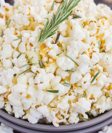 This Rosemary Garlic Popcorn is drizzled with a buttery mix filled with fresh rosemary and a hint of garlic. Simple, easy, and perfect for on-the-go entertaining, this crunchy snack is sure to be the hit of any party!