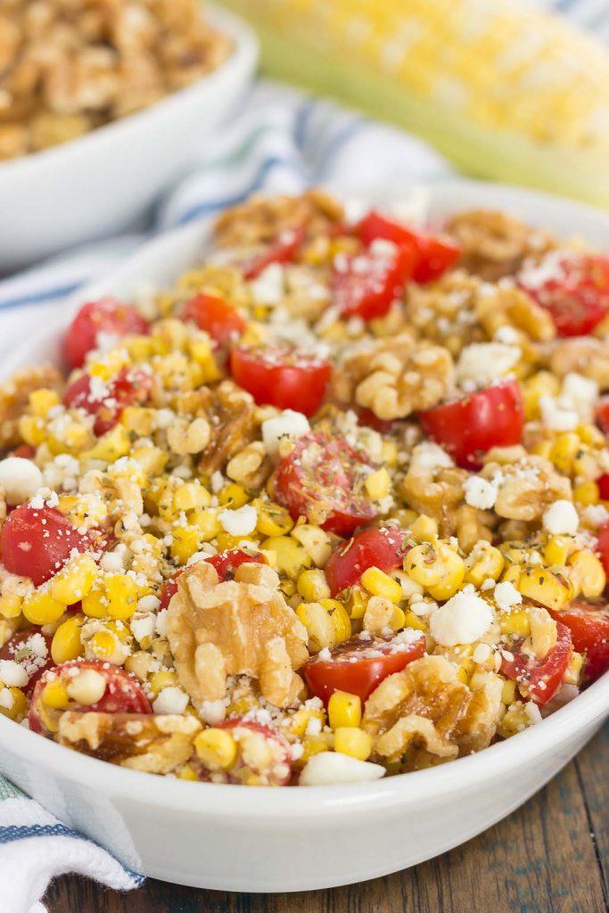 A large white serving platter of corn tomato feta salad.