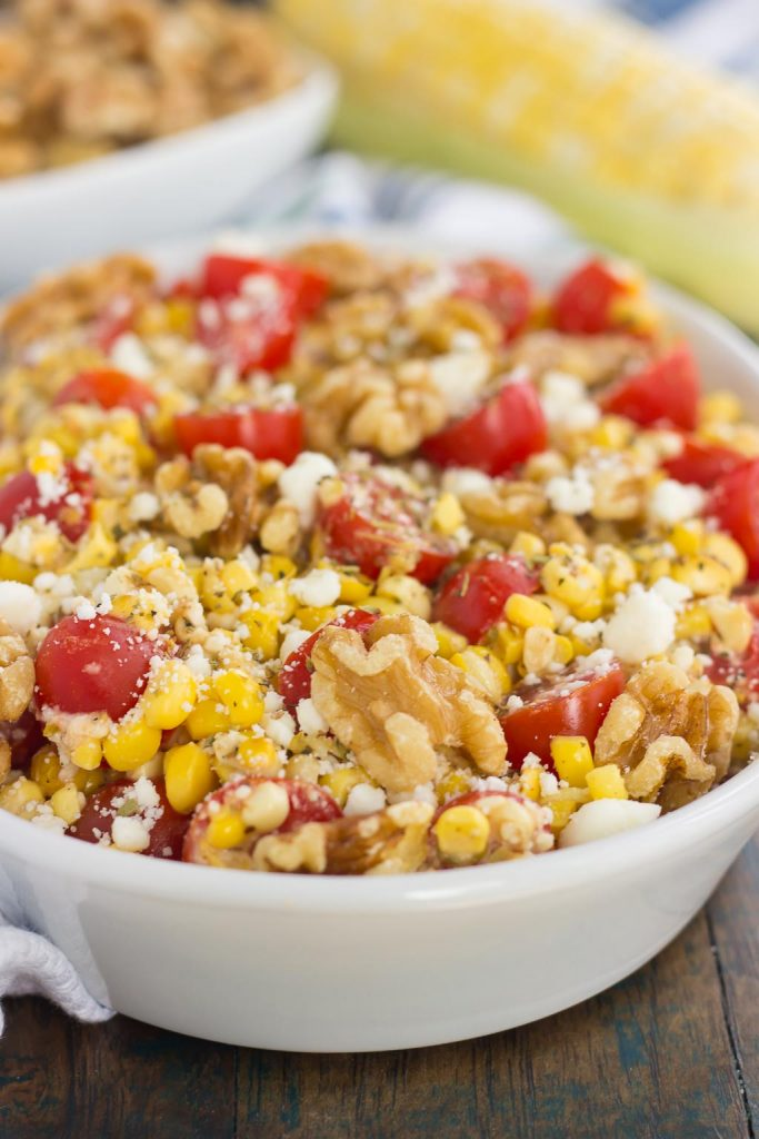 sweet corn salad with walnuts and tomatoes in a white serving platter.