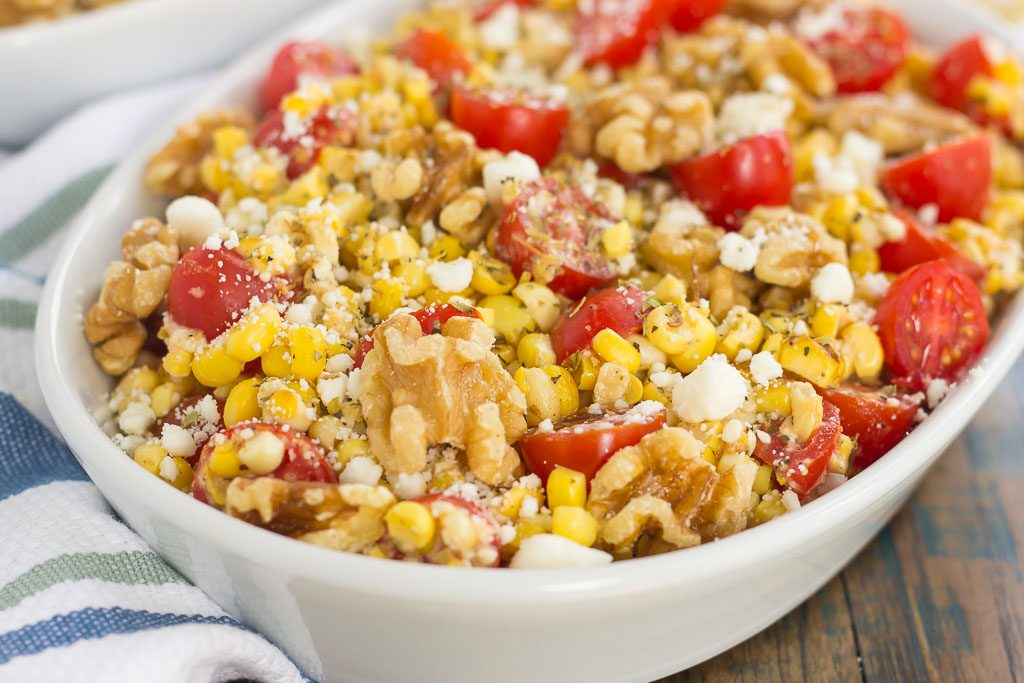 A white serving platter of corn salad with feta.