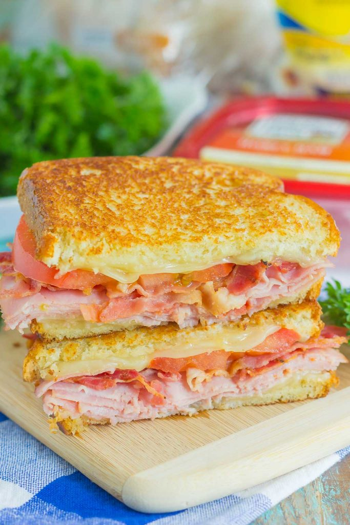 Thinly sliced honey ham, swiss cheese, fresh tomatoes, and crispy bacon are packed between fresh slices of bread that are grilled to perfection. With just six ingredients and hardly any prep work, you can have this Grilled Ham and Swiss Sandwich ready to be devoured in no time! #sandwich #ham #hamsandwich #hamswiss #grilledcheese #grilledhamswiss #lunch #dinner