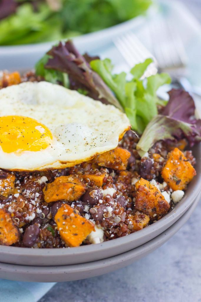 This Roasted Parmesan Sweet Potato Quinoa Bowl is a deliciously simple dish that is perfect for a light lunch or dinner. Filled with roasted sweet potatoes, hearty quinoa, black beans, feta cheese, and a fried egg, this bowl is jam-packed with flavor and so easy to make! #sweetpotatoes #sweetpotatorecipe #quinoabowl #quinoabowlrecipes #falldish #fallrecipes #fallbreakfasts #fallbreakfastideas #breakfast #breakfastrecipes #recipe