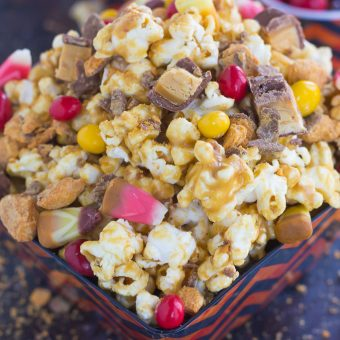 This Peanut Butter Candy Popcorn is the perfect sweet and salty snack to satisfy your sweet tooth! Fresh popcorn is coated with a creamy peanut butter mixture and then tossed with a variety of candies. It makes the best snack to munch on during Halloween, and is also a great way to use up that leftover candy!