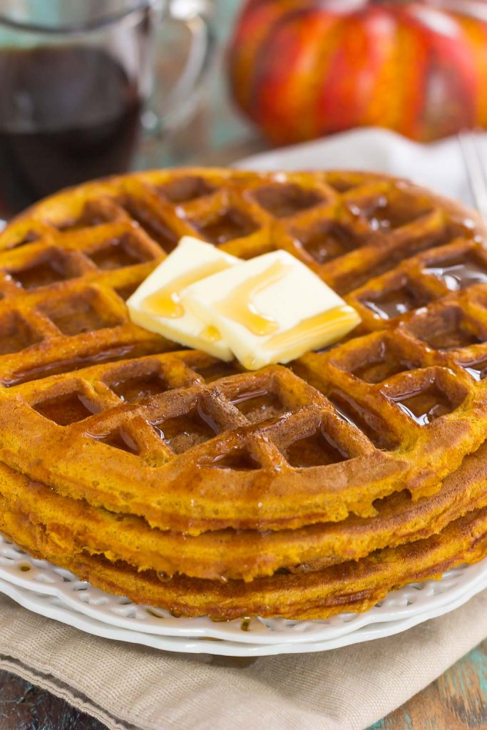 These Pumpkin Spice Waffles are crispy on the outside, tender on the inside, and filled with cozy fall flavors. You can satisfy your craving for pumpkin with this easy breakfast that's sure to be a favorite all year long! #waffles #wafflerecipe #pumpkinrecipe #pumpkinwaffles #pumpkinbreakfast #breakfast #breakfastrecipes