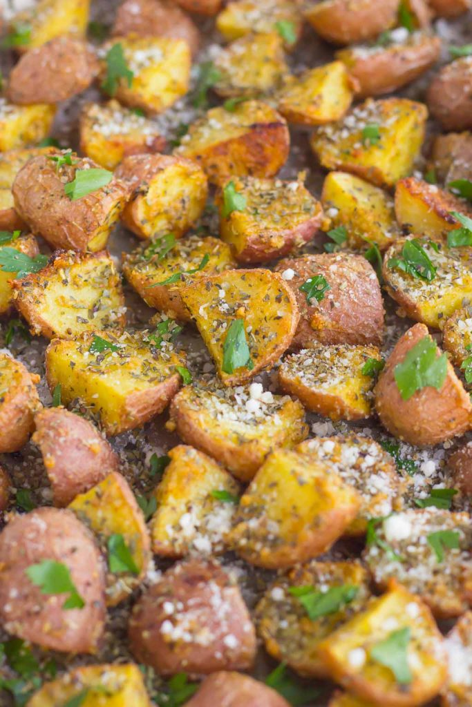 These Herb Roasted Potatoes are seasoned with Parmesan cheese, a variety of spices, and baked to perfection. Crispy on the outside and tender on the inside, this easy side dish comes together in minutes and is sure to be the hit of the dinner table! #potatoes #roastedpotatoes #herbpotatoes #herbroastedpotatoes #sidedish #easysidedish #roastedvegetables
