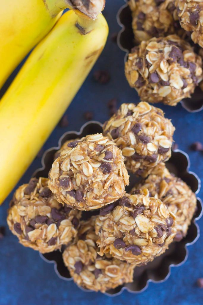 overhead view of no bake banana energy bites in a metal dish next to a bunch of bananas