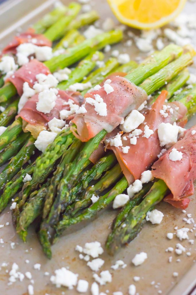 prosciutto wrapped asparagus sprinkled with feta on a baking sheet