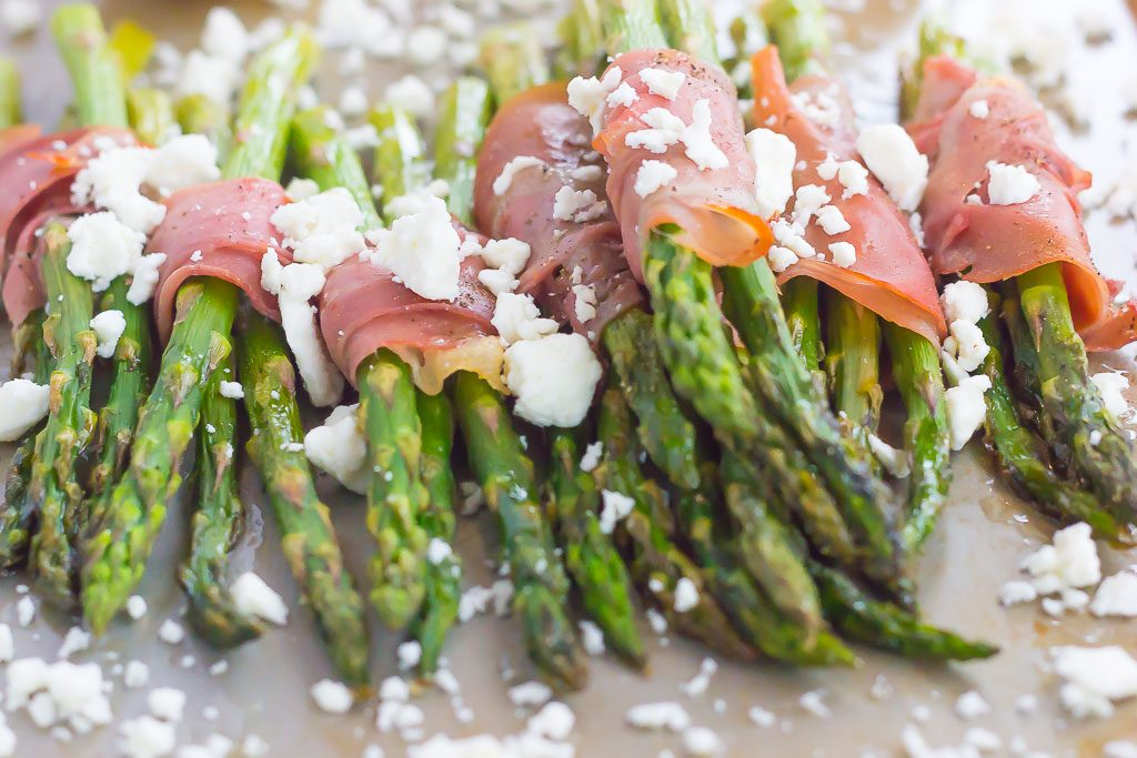 prosciutto wrapped asparagus bundles sprinkled with feta on a baking sheet