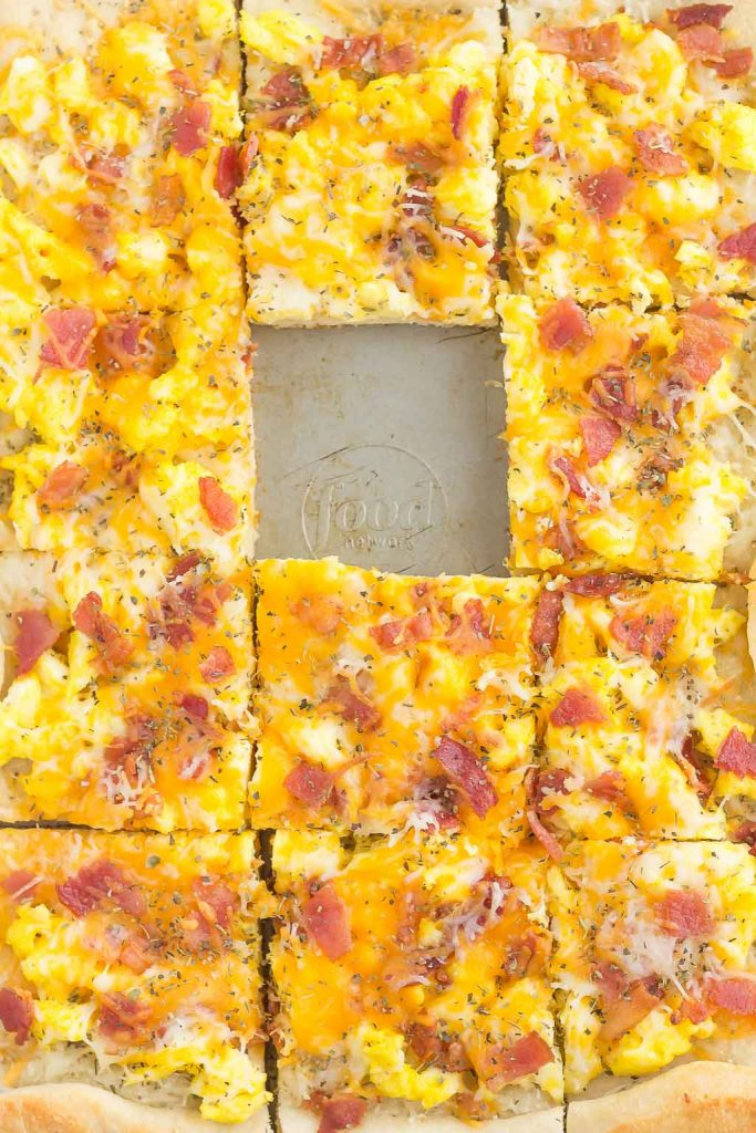 Overhead view of a sliced scrambled egg breakfast pizza with one square missing.