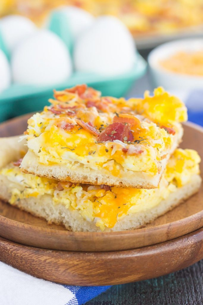 Two slices of a bacon and eggs breakfast pizza on a stack of wooden plates.