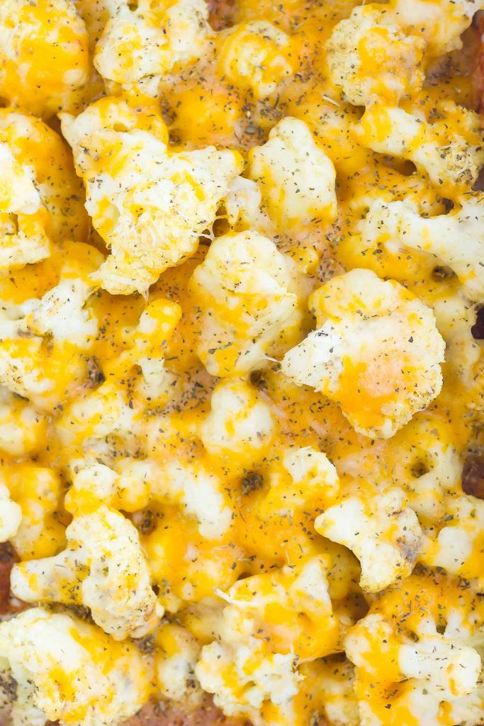 This Baked Cheesy Cauliflower is delicious way to jazz up your favorite veggie. Cauliflower florets are drizzled with olive oil, a blend of seasonings, and topped with two kinds of cheese. Baked until tender and oozing with flavor, this easy vegetable will quickly become a new mealtime favorite!