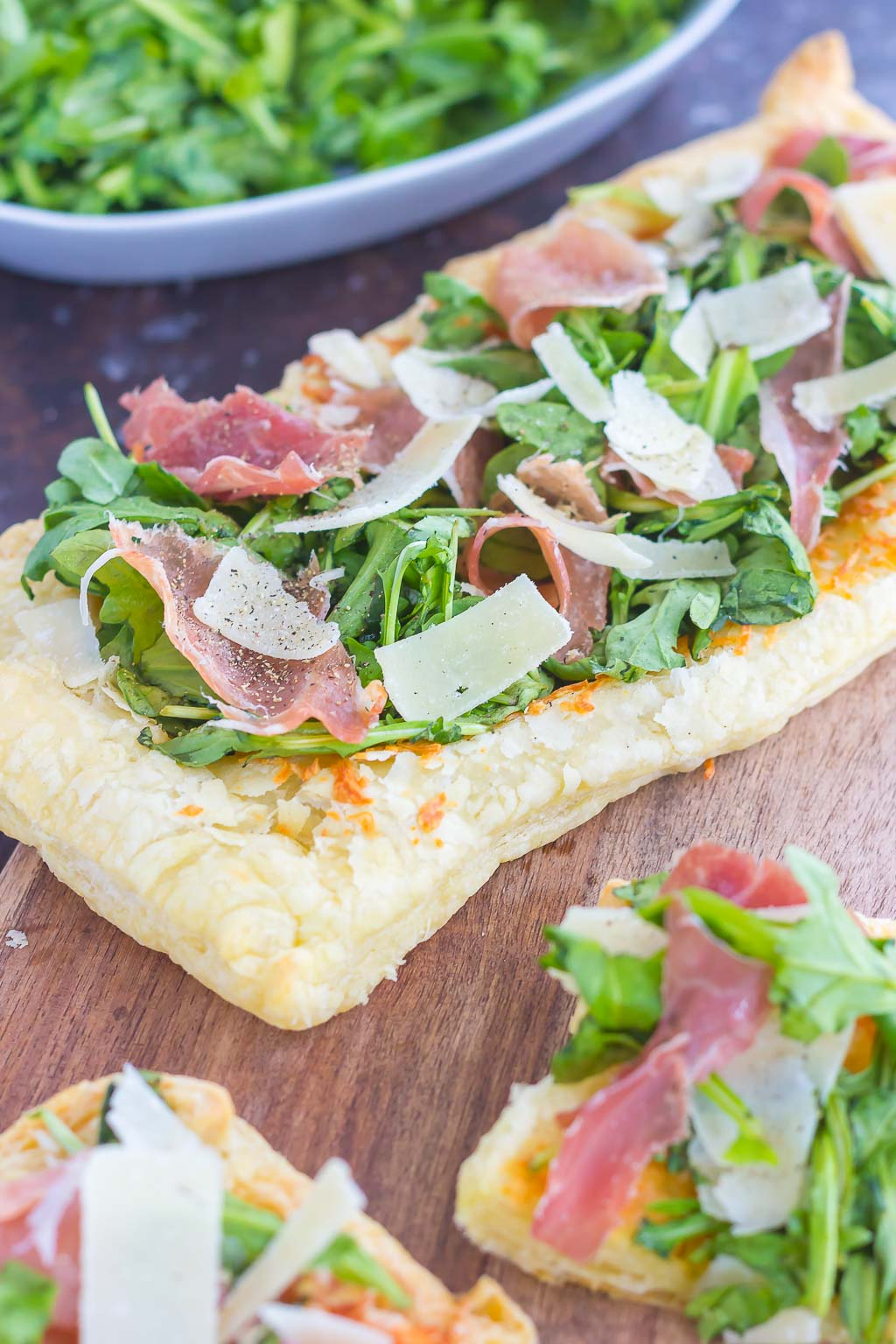 This Arugula and Prosciutto Puff Pastry Pizza is easy to make and ready in about 20 minutes. Puff pastry dough is drizzled with olive oil, and then topped with mozzarella cheese, fresh arugula, salty prosciutto and some shaved Parmesan cheese. Simple, fresh, and bursting with flavor, this lighter pizza is perfect for busy weeknights and is sure to be a mealtime winner