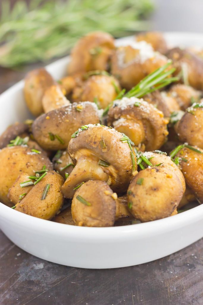 These Roasted Mushrooms with Garlic and Rosemary are loaded with a savory mixture of herbs and then baked until golden. Fast, fresh and easy to make, these mushrooms take less than 30 minutes from start to finish! #mushrooms #roastedmushrooms #mushroomrecipe #garlicmushrooms #rosemarymushrooms #sidedish #easysidedish