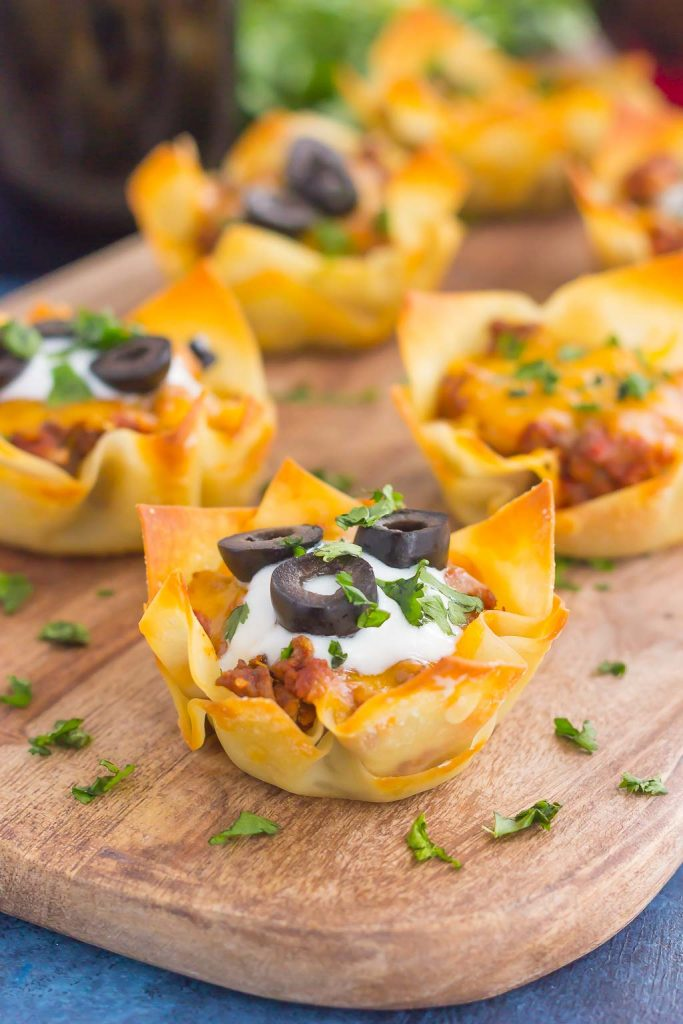 These Cheesy Taco Cups are the perfect game day snack. Your favorite taco ingredients are layered in wonton wrappers and baked in mini form. Easy to make and even better to eat, you'll enjoy these handheld cups that are packed with so much flavor!