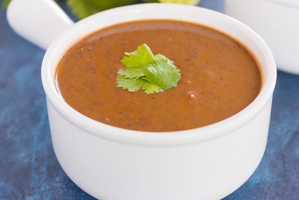 Creamy black bean soup in a white soup bowl.