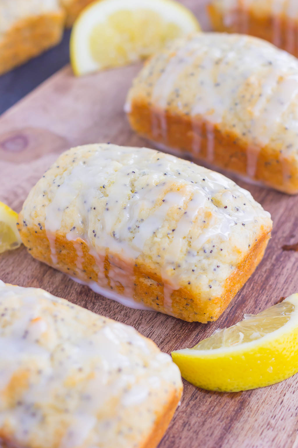 mini lemon lemon poppy seed bread loaves with glaze lined up on a wood board
