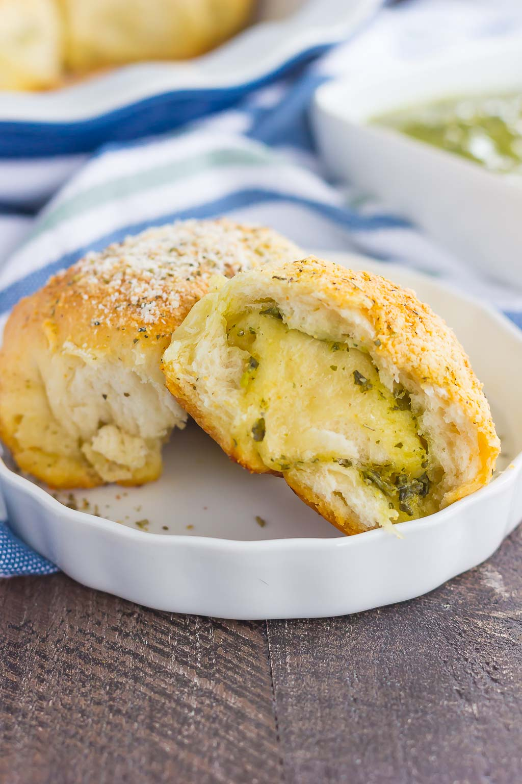 These Stuffed Cheesy Pesto Rolls are an easy dish to make for those hungry dinner guests. Soft and buttery rolls are filled with pesto sauce and mozzarella cheese, and then baked until golden. Crispy on the outsize and oozing with flavor on the inside, this simple roll is sure to wow even the pickiest of eaters!