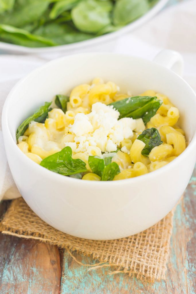 All it takes is just one mug and 5 minutes to make this Microwave Mug Spinach and Feta Macaroni and Cheese. Tender pasta, mozzarella and feta cheeses and a sprinkling of spinach create an easy, cheesy, and oh-so delicious single serving recipe for the best macaroni and cheese! #macncheese #macaroniandcheese #macandcheese #spinach #feta #fetamacandcheese #pasta #microwave #dinner