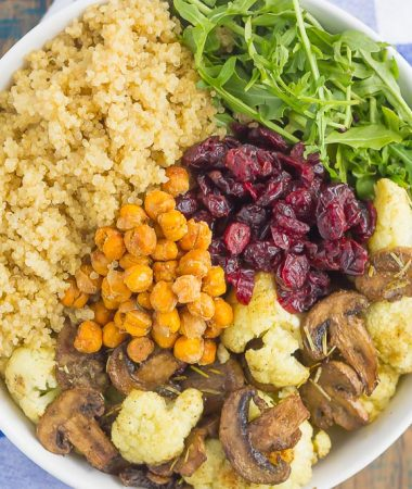 This Roasted Cauliflower, Mushroom and Chickpea Quinoa Bowl is a quick and easy meatless meal that is sure to please everyone. Hearty quinoa is tossed with roasted cauliflower, mushrooms, chickpeas, and arugula, all tossed in a savory white balsamic dressing. This healthier meal is ready in just 30 minutes and packed with delicious superfoods!
