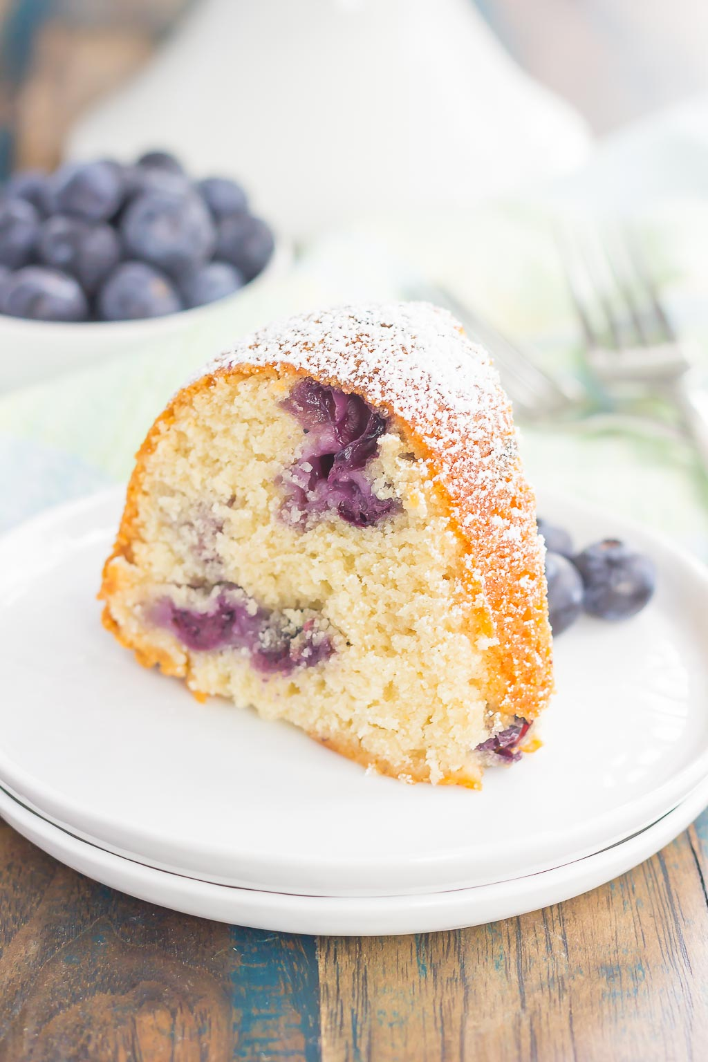 A slice of blueberry yogurt cake on a white plate. A dish of blueberries rest in the background.