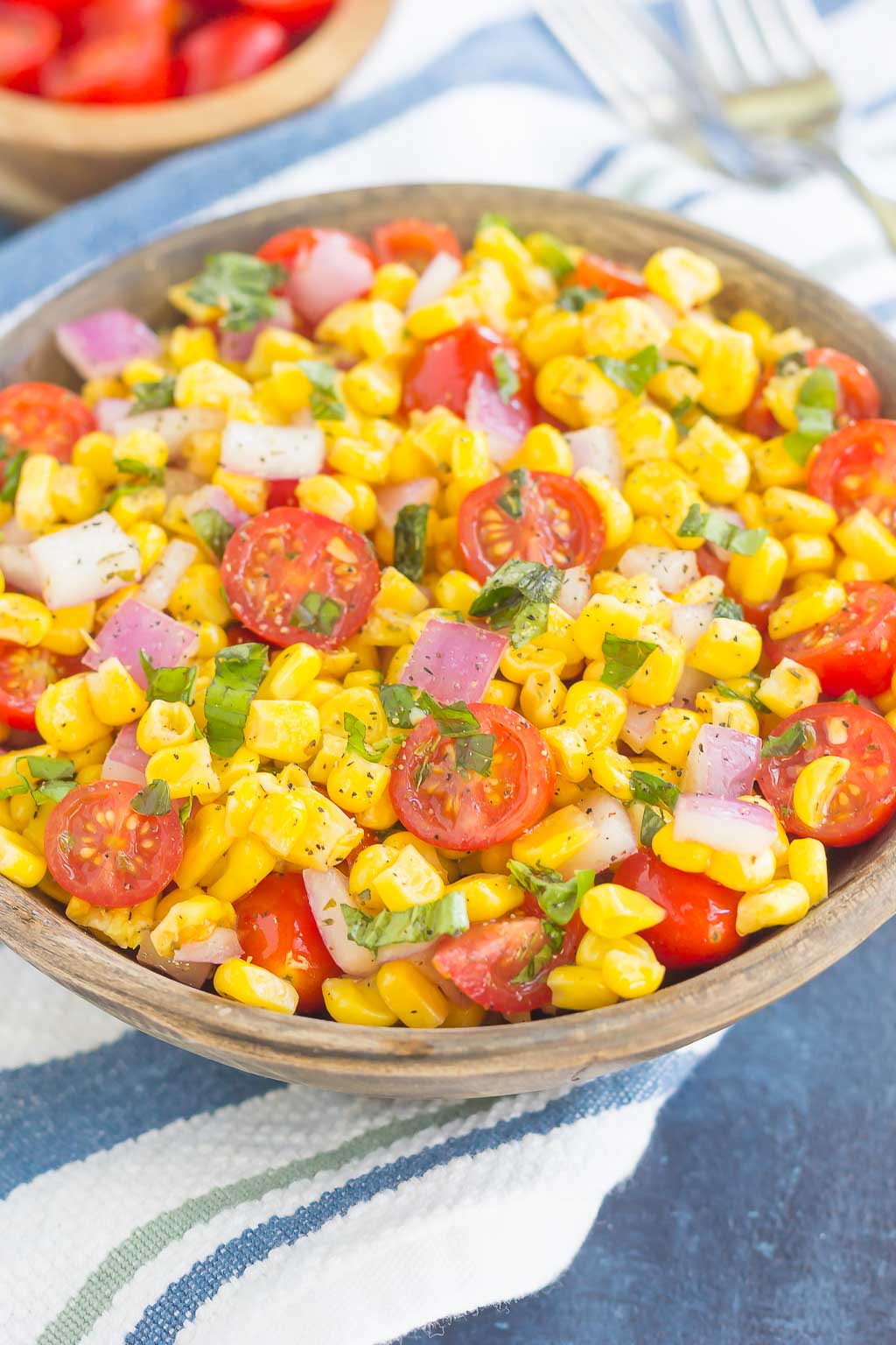 With fresh corn cut straight from the cob, cherry tomatoes, spices, and a light dressing, this Corn and Tomato Salad is perfect for a summer lunch or dinner! #corn #cornsalad #tomato #tomatosalad #corntomatosalad #salad #saladrecipe #summersalad